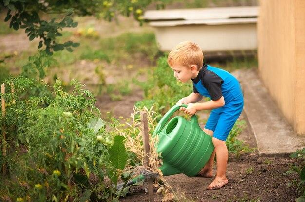 Junge nährt einen garten mit einer grünen gießkanne nahaufnahme.