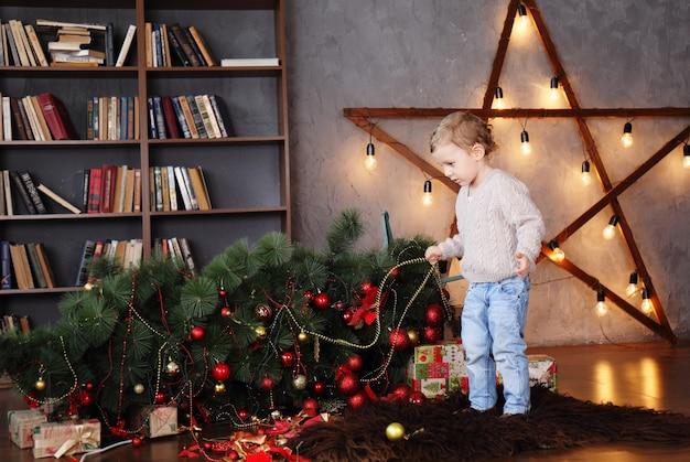 Junge nahe einem gefallenen weihnachtsbaum. weihnachtskonzept