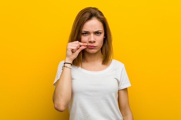 Junge natürliche kaukasische frau mit den fingern auf den lippen, die ein geheimnis halten.