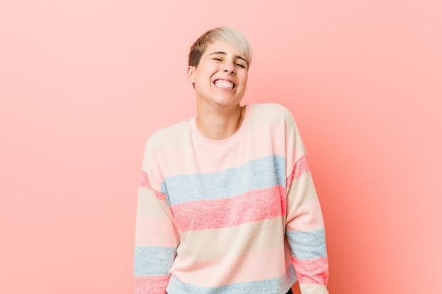 Junge natürliche kurvige frau lacht und schließt die augen, fühlt sich entspannt und glücklich.