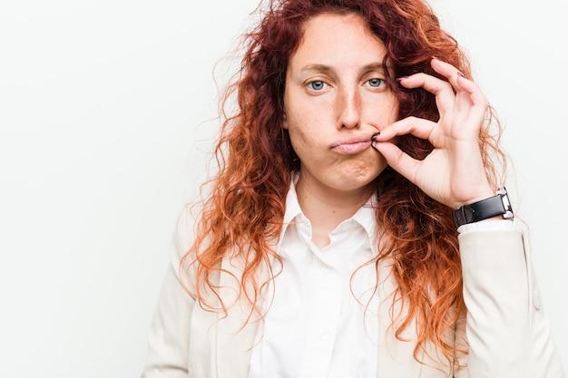 Junge natürliche rothaarige geschäftsfrau mit den fingern auf den lippen, die ein geheimnis halten