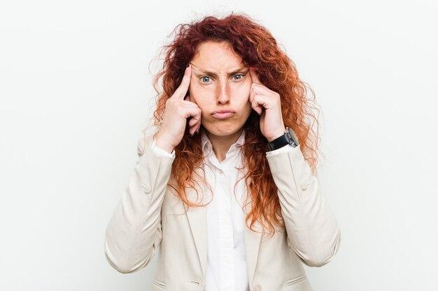 Junge natürliche rothaarigegeschäftsfrau konzentrierte sich auf eine aufgabe und hielt die zeigefinger, die kopf zeigen