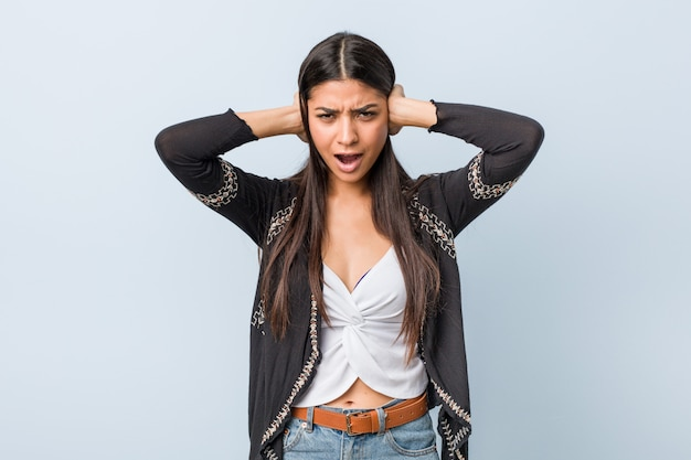 Junge natürliche und hübsche arabische frau, die ohren mit händen bedeckt, die versuchen, nicht zu lautes geräusch zu hören.