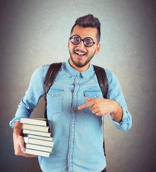 Junge nerd, der bücher für eine prüfung studiert