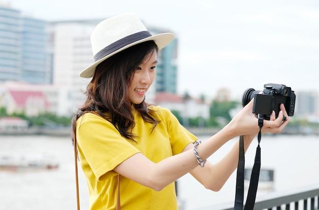 Junge nette asiatische frau in der zufälligen art, die draußen selfie mit kamera in der städtischen stadt macht