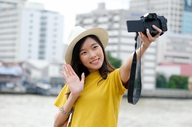 Junge nette asiatische frau in der zufälligen art unter verwendung der kamera zum selfie