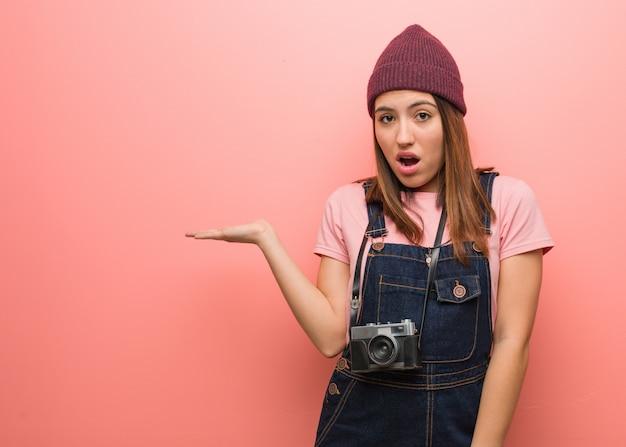 Junge nette fotograffrau, die etwas auf palmenhand hält
