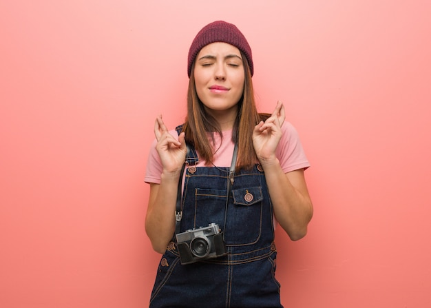 Junge nette fotograffrau, die finger für das haben des glücks kreuzt