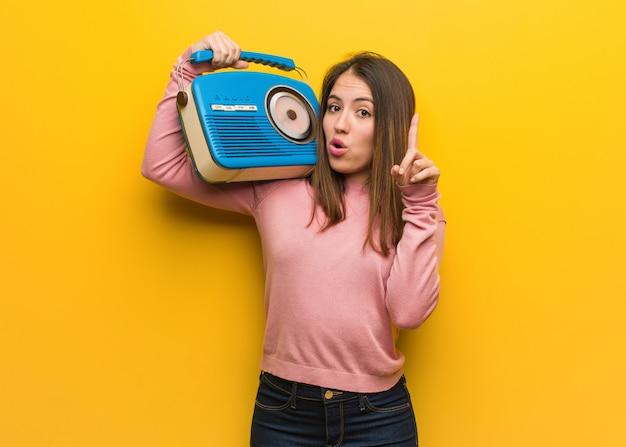 Junge nette frau, die einen weinleseradio hat eine großartige idee, konzept der kreativität hält