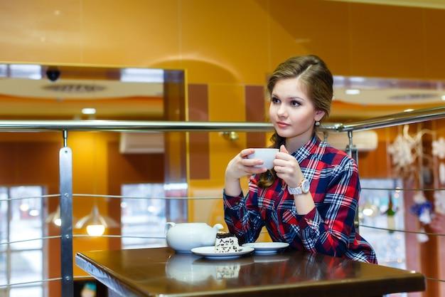 Junge nette frau in einem karierten hemd, das tee in einem café trinkt
