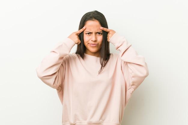 Junge nette hispanische jugendlichfrau konzentrierte sich auf eine aufgabe und hielt die zeigefinger, die kopf zeigen.