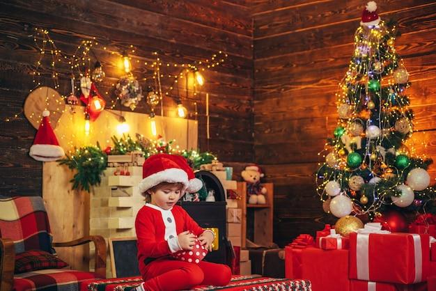 Junge nettes kind fröhliches stimmungsspiel nahe weihnachtsbaum. familienurlaub. frohe und helle weihnachten. schönes baby, genießen sie weihnachten. kleines kind des weihnachtsmannes feiert weihnachten zu hause. kindheitserinnerungen.