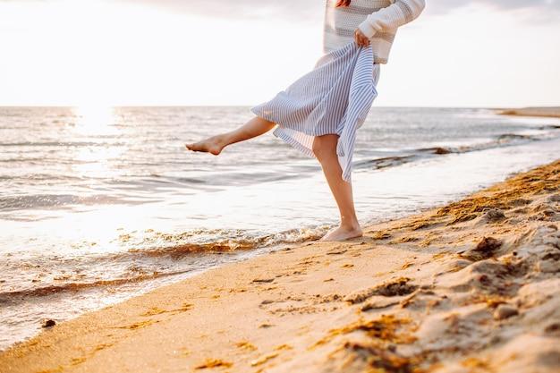 Junge, nicht erkennbare frau im kleid geht allein am leeren sandstrand bei sommersonnenuntergang am meeresufer.
