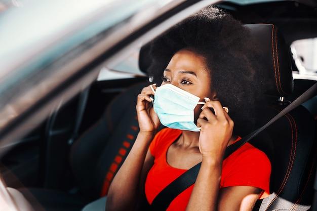 Junge niedliche afrikanische frau mit dem kurzen lockigen haar, das im auto sitzt und maske auf setzt. schutz vor coronavirus / covid 19-konzept.
