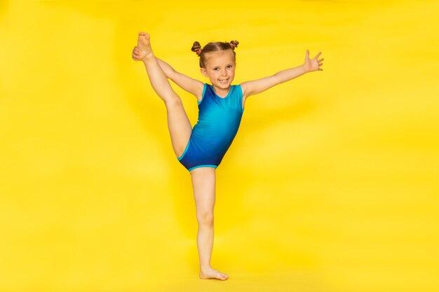 Junge niedliche barfüßige turnerin mit zwei brötchen im blauen sportanzug, der auf gelbem hintergrund mit kopienraum aufwirft.