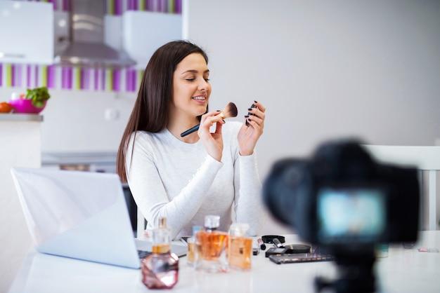 Junge niedliche bloggerin, die ihre präsentation von kosmetischen produkten filmt. sitzen in einem hellen raum vor der kamera.