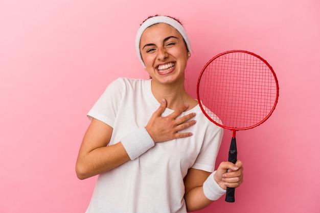 Junge niedliche blonde kaukasische frau, die einen badmintonschläger lokalisiert auf rosa hintergrund hält, lacht laut heraus und hält hand auf brust.