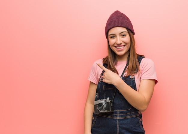 Junge niedliche fotograffrau, die lächelt und zur seite zeigt