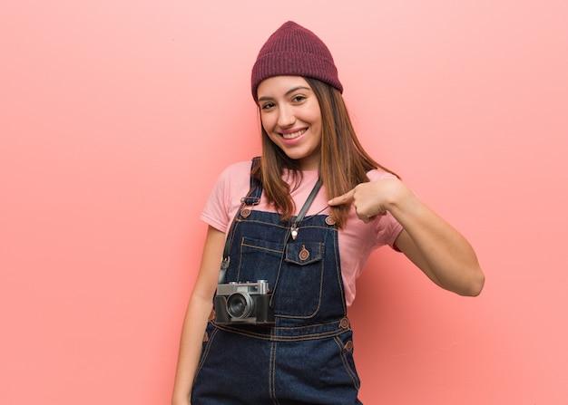 Junge niedliche fotograffrau person, die von hand auf eine leere stelle des hemdes zeigt, stolz und zuversichtlich