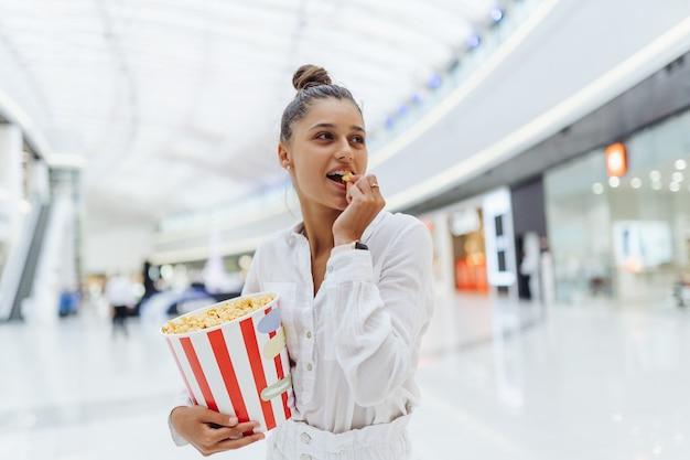 Junge niedliche frau, die popcorn im hintergrund des einkaufszentrums hält