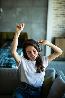 Junge niedliche lächelnde frau, die auf couch tanzt, während sie drahtlose kopfhörer zu hause benutzt