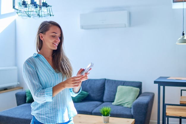 Junge niedliche lässige frau, die klimaanlage benutzt und bequeme temperatur mit fernbedienung an wohnung einstellt