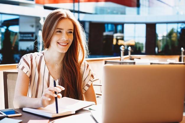 Junge niedliche weibliche beeinflusserin mit roten haaren, die videoinhalt auf ihrem laptop beim sitzen in einem café außerhalb lächelnd tun.