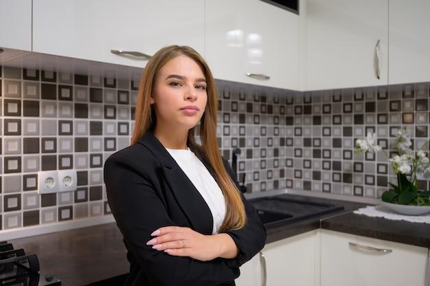 Junge niedliche weibliche designerin bei luxus moderne weiße küche interieur mit sauberem design