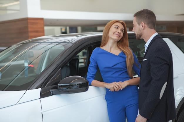Junge noble paare, die luxuriöses auto an der verkaufsstelle kaufen