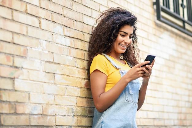 Junge nordafrikanische frau, die draußen mit ihrem intelligenten telefon simst