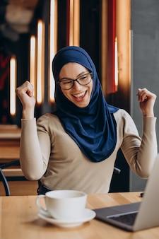 Junge nuslimische frau, die online am computer in einem café arbeitet?