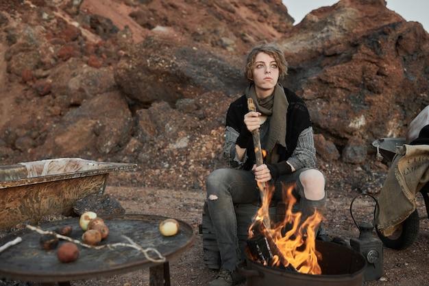 Junge obdachlose frau, die vor dem feuer sitzt und sich draußen das essen kocht