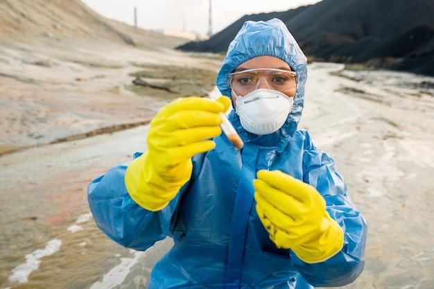 Junge ökologin in atemschutzmaske und brille, die flasche mit einer probe schmutzigen wassers in einem verschmutzten und giftigen industriegebiet betrachtet