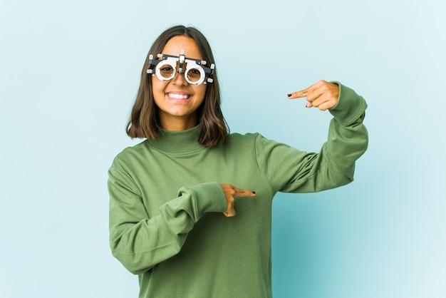 Junge okulistische lateinische frau, die etwas wenig mit zeigefingern hält, lächelnd und zuversichtlich.