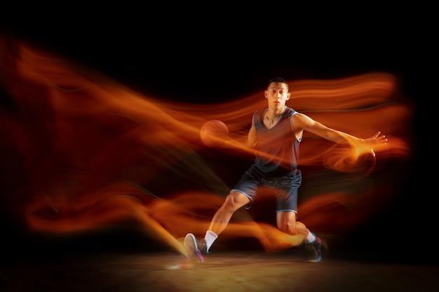 Junge ostasiatische basketballspieler in aktion und springen in gemischtem licht über dunklem studiohintergrund.