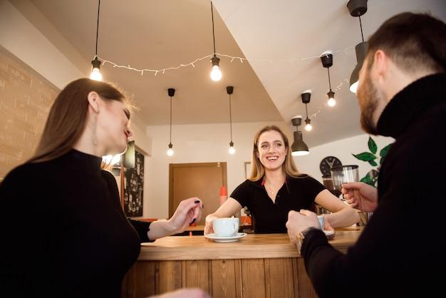 Junge paar kunden, die kaffee von barista im café nehmen.