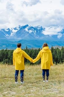 Junge paar wanderer mann und frau halten hände und schauen auf die berge auf einer reise