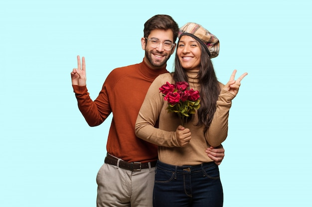 Junge paare am valentinsgrußtag, der eine geste des sieges tut
