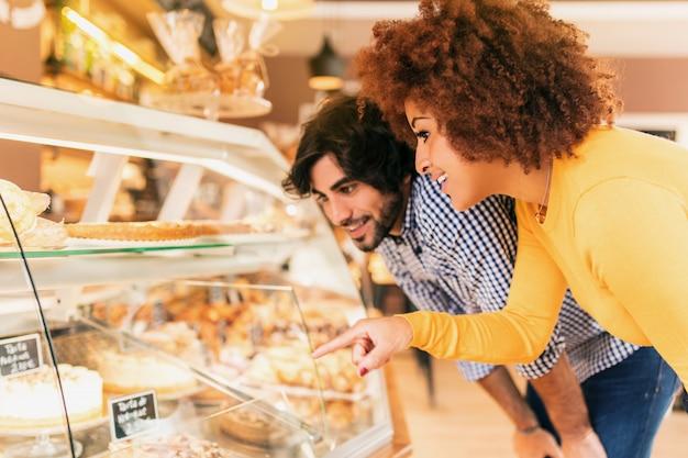 Junge paare an der bäckerei, den schaukasten betrachtend, um etwas zu essen. sie fühlen sich glücklich.
