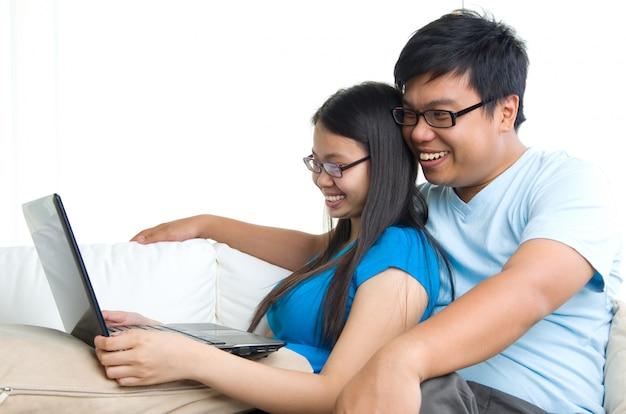 Junge paare auf sofa mit tablet-computer