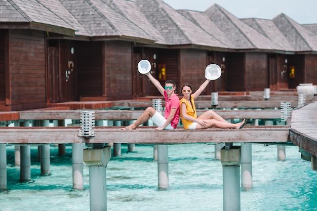 Junge paare auf strandanlegestelle in tropeninsel in den flitterwochen