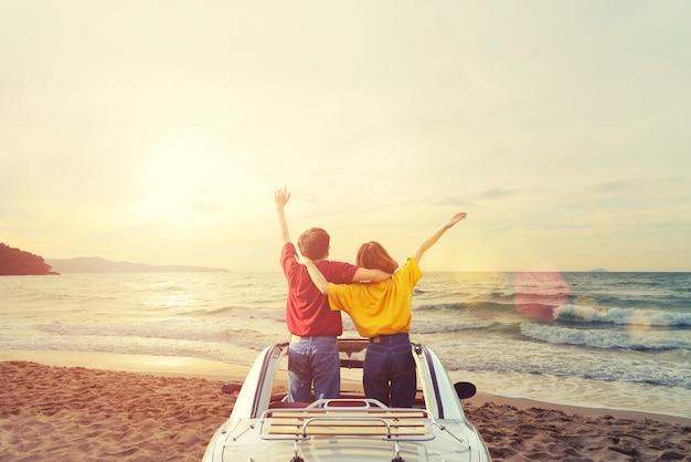 Junge paare des glückes im auto auf dem tropischen strand bei sonnenuntergang. sommerreise- und ferienzeitkonzept.