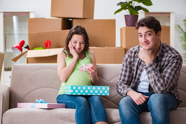 Junge paare des mannes und der schwangeren frau mit geschenkbox