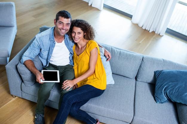 Junge paare des porträts, die auf sofa sitzen und digitale tablette verwenden