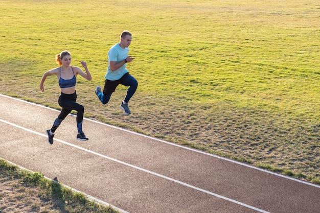 Junge paare des sitzsportlerjungen und -mädchens, die beim auf roten bahnen des allgemeinen stadions draußen trainieren laufen.
