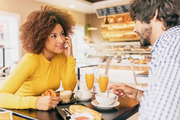 Junge paare, die am café frühstücken, sie trinken tee und kaffee und einen orangensaft.
