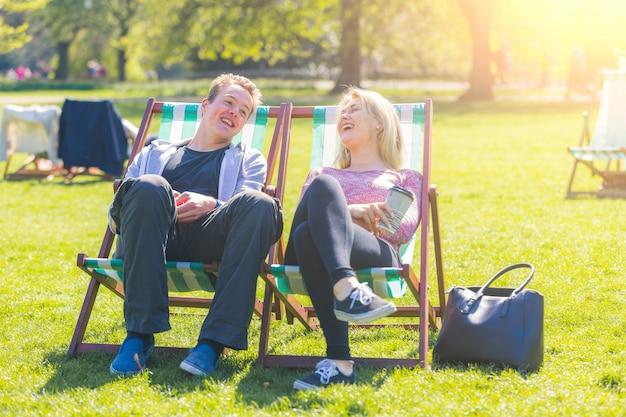 Junge paare, die am park an einem sonnigen tag sich entspannen
