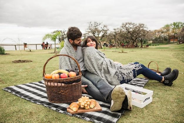Junge paare, die am picknick im park genießen