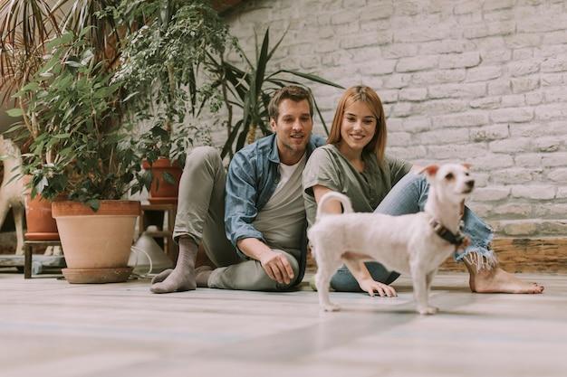 Junge paare, die am rustikalen wohnzimmerboden sitzen und mit hund spielen