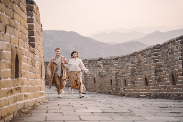 Junge paare, die an der chinesischen mauer laufen und wirbeln